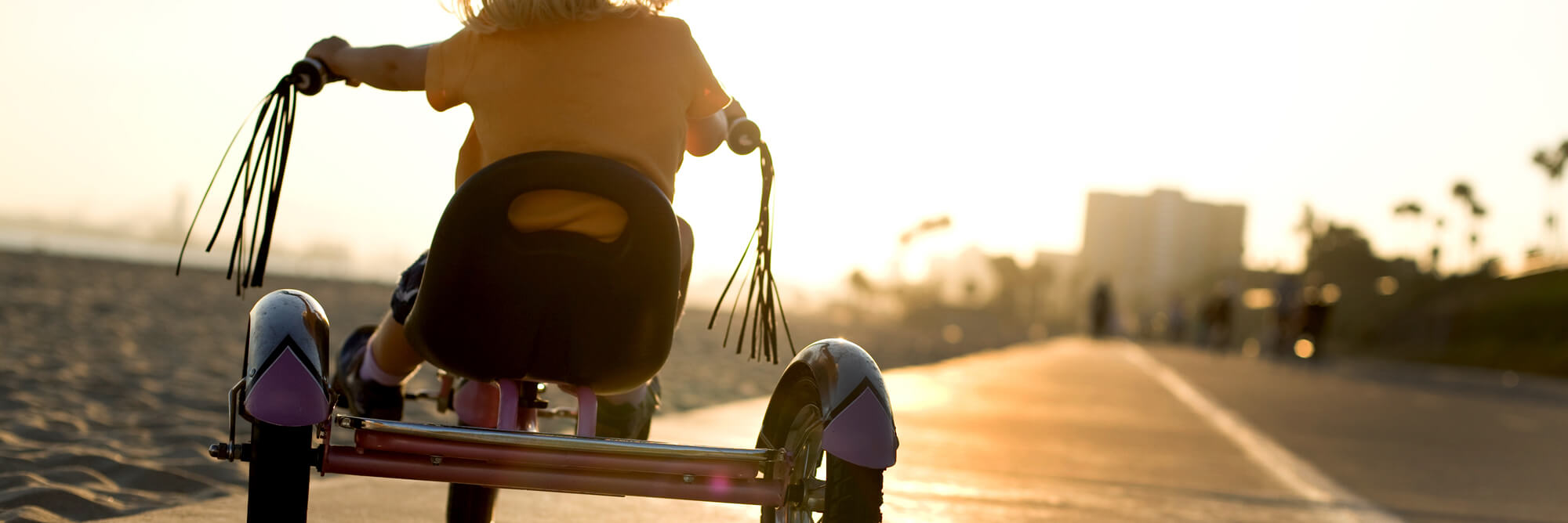 A child riding a tricycle as the sun sets in the background