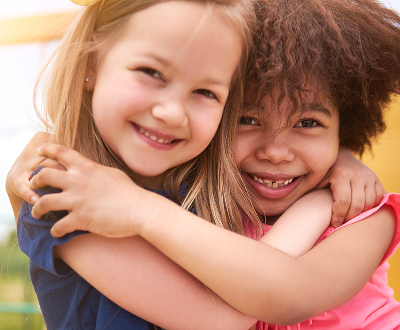 Two young girls hugging and smiling