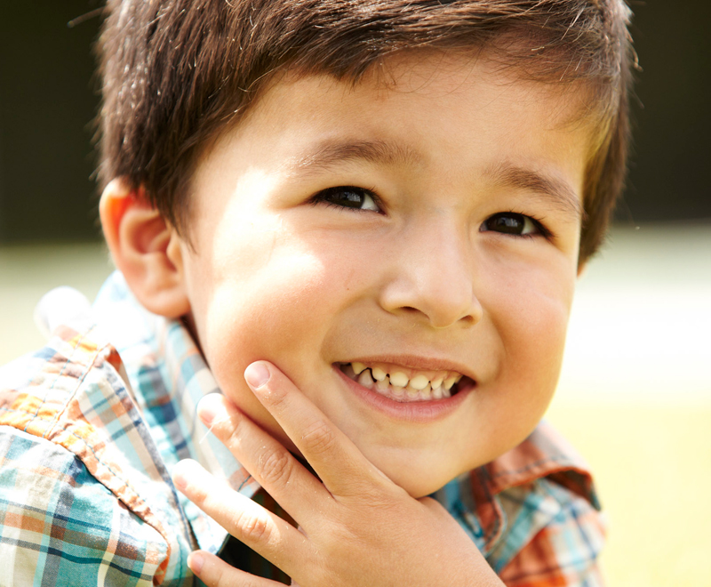 Young boy with hands around chin smiling