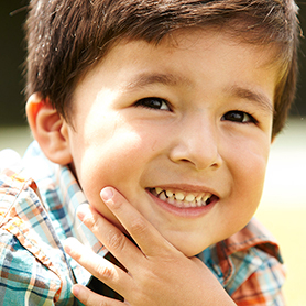 A young boy with his hand around his chin, smiling